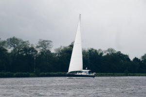 Ein Segler auf dem Nord-Ostsee-Kanal unter Segeln kommt entgegen.